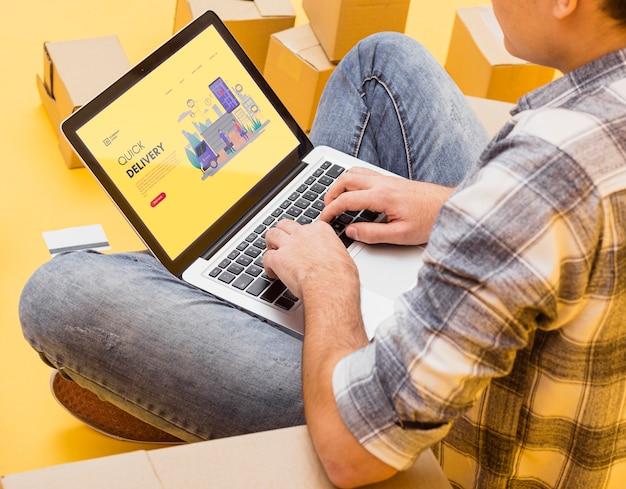 Мужчина держит ноутбук макет вокруг посылки Бесплатные Psd