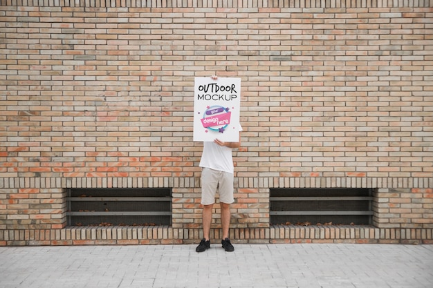 Man holding poster mockup in front of brick wall Free Psd