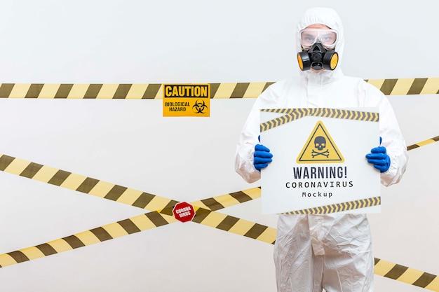 警告コロナウイルスのモックアップを保持している防護服の男 無料 Psd