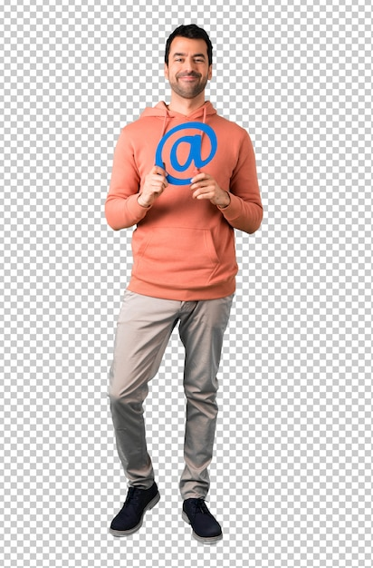 Man in a pink sweatshirt holding icon of at dot com Premium Psd