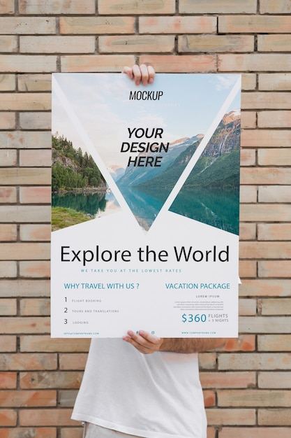 Man presenting poster mockup in front of brick wall Free Psd