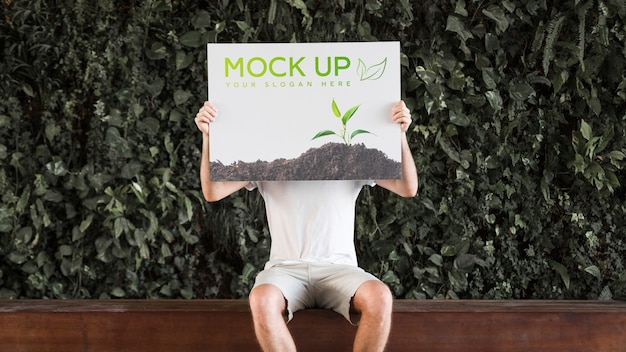 Man presenting poster mockup in front of leaves Free Psd