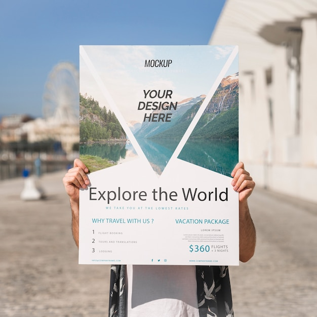 Man presenting poster mockup in front of park Free Psd