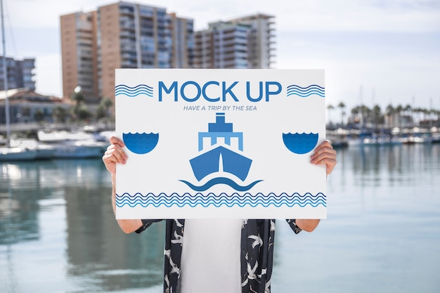 Man presenting poster mockup in front of water Free Psd