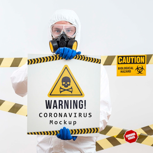 Man in protection suit holding a warning coronavirus mock-up Free Psd