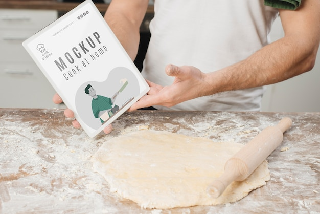Man rolling dough in the kitchen and holding book Free Psd