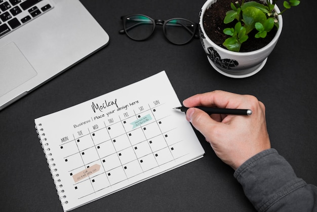 Mano dell'uomo che scrive sul calendario Psd Gratuite