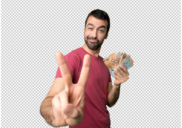 Man taking a lot of money smiling and showing victory sign Premium Psd