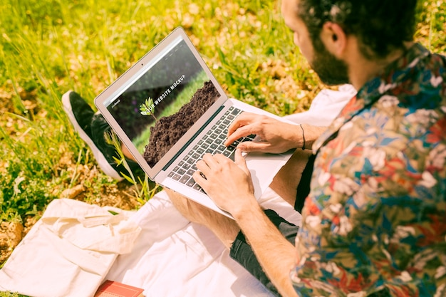 Man using laptop mockup in nature Free Psd