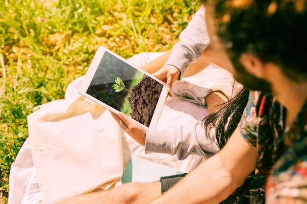 Man using tablet mockup in nature Free Psd