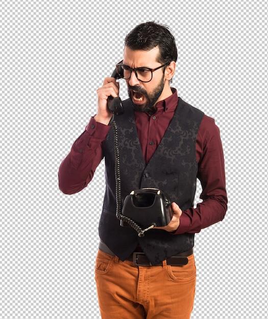 Man wearing waistcoat talking to vintage phone Premium Psd