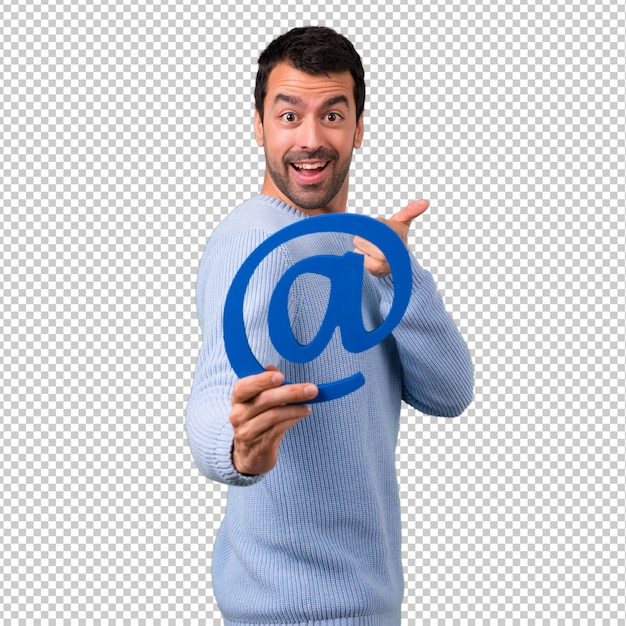 Man with blue sweater holding icon of at dot com Premium Psd
