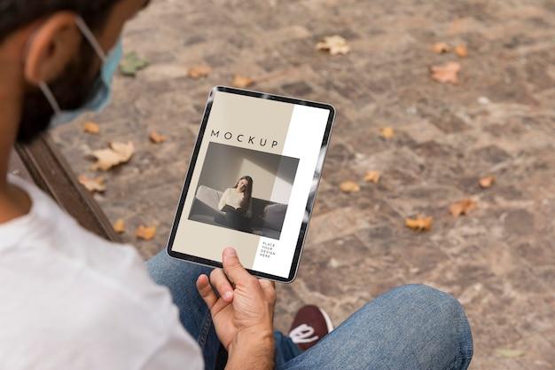 Uomo con la maschera sul libro di lettura di strada su tablet Psd Gratuite