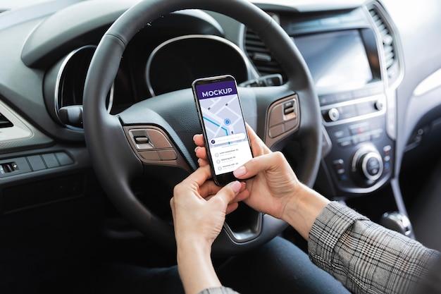 車の中で電話のモックアップを持つ男 Premium Psd