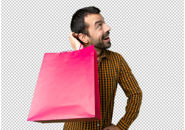 Man with shopping bags thinking an idea while scratching head Premium Psd
