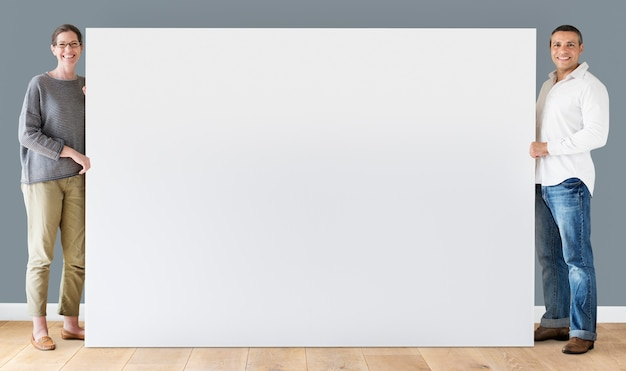 Man and woman holding blank board Premium Psd