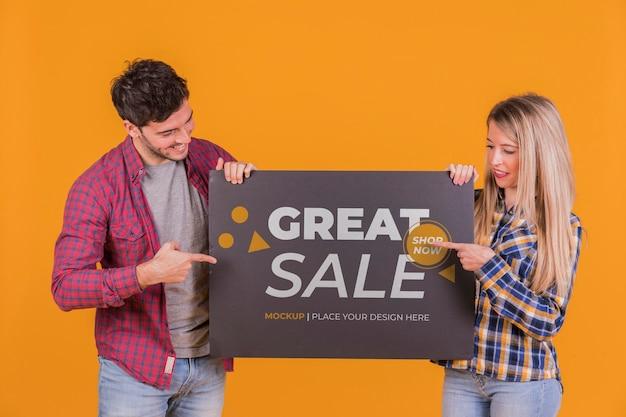 Uomo e donna che tengono un modello di concetto del segno Psd Gratuite