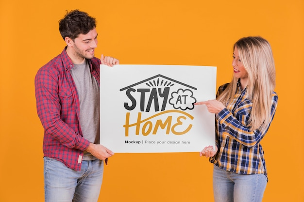 Man and woman holding a sign concept mock-up Free Psd
