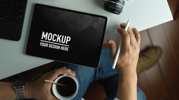 Человек, работающий над макетом экрана планшета, попивая чашку кофе в рабочем пространстве Premium Psd