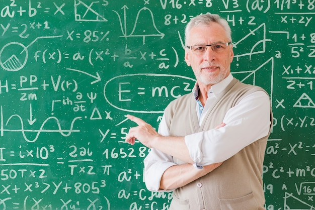 A professor infront of a blackboard with math equations.