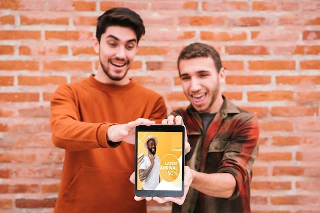 Medium shot happy guys holding up tablet Free Psd