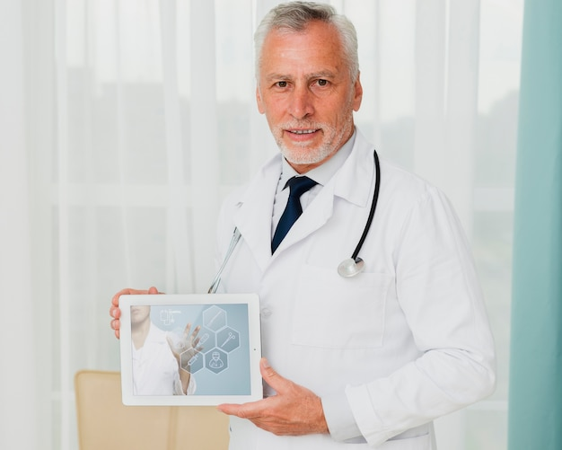Medium shot of male doctor holding a tablet Free Psd