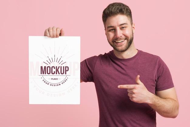 Colpo medio dell'uomo che tiene una carta mock-up di cancelleria Psd Gratuite