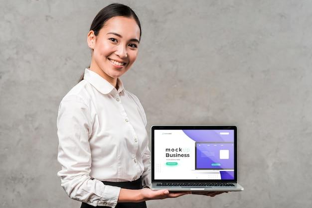 Средний выстрел женщина держит ноутбук Бесплатные Psd
