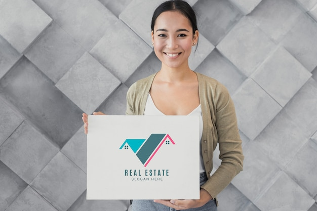 Medium shot of woman holding a poster with real estate Free Psd