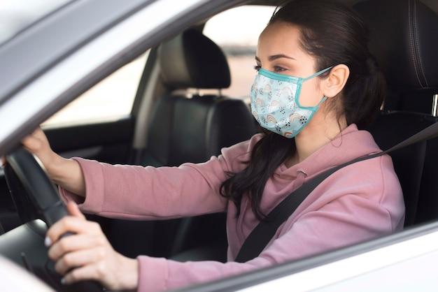Medium shot woman with mask driving Free Psd