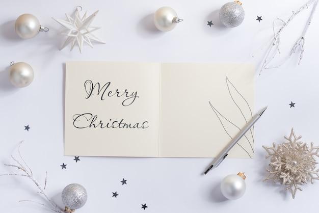 白いクリスマスボールとメリークリスマスグリーティングカードのモックアップ Premium Psd