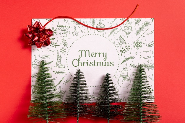 Merry christmas mock-up paper with pine trees Free Psd