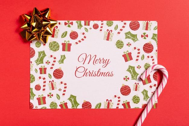 Carta mock-up di buon natale con canna da zucchero e fiocco Psd Gratuite