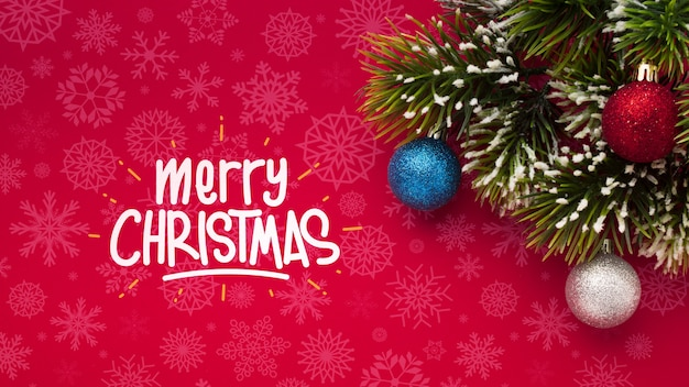 Merry christmas and pine leaves on christmas red background Free Psd