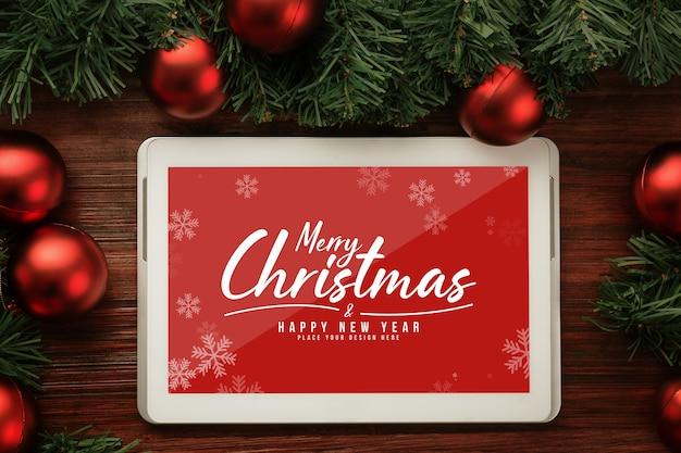松の葉の装飾が施されたメリークリスマスタブレットコンピューターのモックアップ Premium Psd