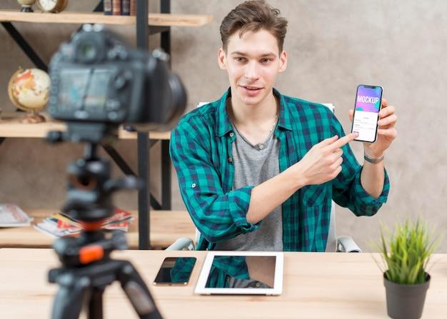 Mid shot blogger holding mock-up phone Free Psd