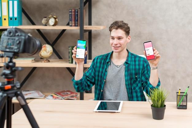 Mid shot blogger holding mock-up phones Free Psd