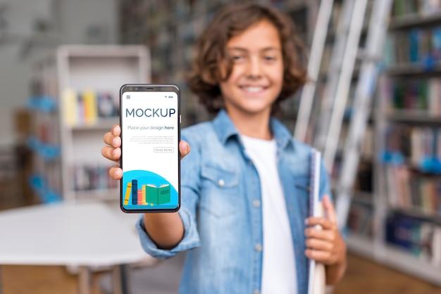 Мальчик в середине кадра в библиотеке показывает макет телефона Premium Psd