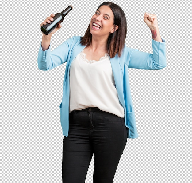 Middle aged woman happy and fun, holding a bottle of beer, feels good after an intense day of work, ready to watch a soccer match on television Premium Psd