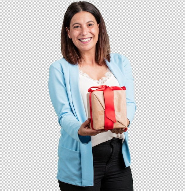 Middle aged woman happy and smiling, holding a nice gift, excited and full, celebrating a birthday or a featured event Premium Psd