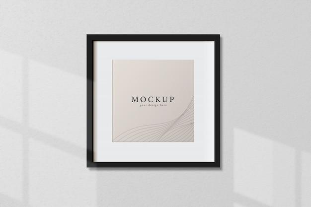 最小限の空の正方形の黒いフレームの画像が窓の光と影で白い壁の背景に掛かっているモックアップ。ベクトル図を分離します。 Premium Psd