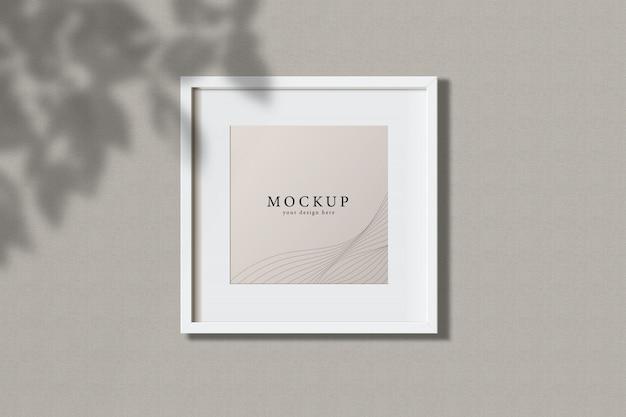Минимальная пустая квадратная белая рамка изображение макет висит на фоне стены с листьями окна. изолировать векторные иллюстрации. Premium Psd