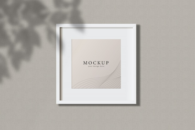 Minimal empty square white frame picture mock up hanging on wall background with leaves window. isol