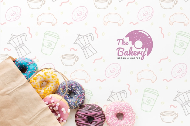Mix of colorful donuts in paper bag with mock-up Free Psd