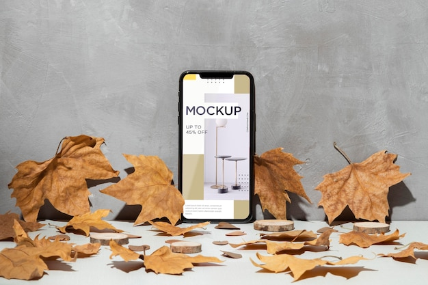 나뭇잎으로 둘러싸인 벽에 기대어 휴대 전화 모형 무료 PSD 파일