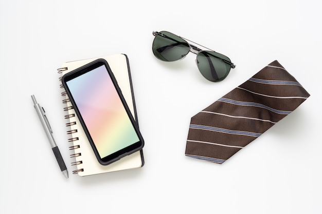 Mobile phone mockup smartphone with gentleman accessories on white desk table. Premium Psd
