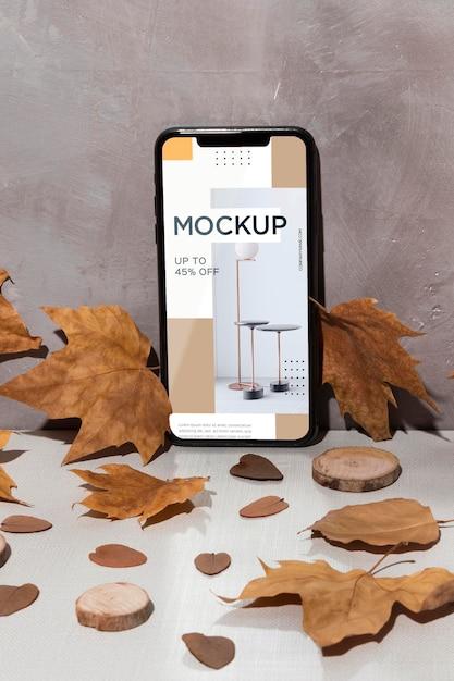 葉に囲まれたテーブルの上に立っている携帯電話のモックアップ 無料 Psd