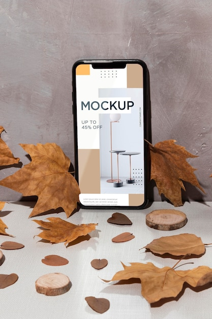 Mobile phone mockup standing on the table surrounded by leaves Free Psd