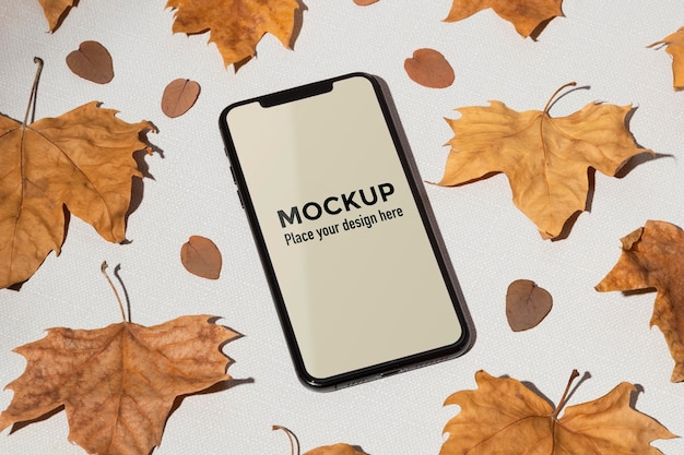 Mobile phone mockup on the table surrounded by leaves Premium Psd