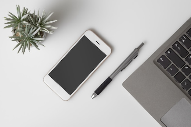 Mobile phone mockup, top view of white office desk table or desktop with mockup blank screen smartphone and computer laptop. Premium Psd